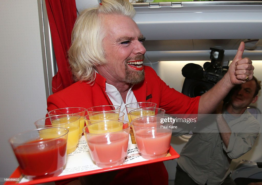 Sir Richard Branson asks passengers for a thumbs up to spill drinks onto Tony Fernandes prior to his flight to Kuala Lumpur at Perth International Airport on May 12, 2013 in Perth, Australia. Sir Richard Branson lost a friendly bet to AirAsia Group Chief Executive Officer Tony Fernandez after wagering on which of their Formula One racing teams would finish ahead of each other in their debut season of the 2010 Formula One Grand Prix in Abu Dhabi and that the loser would serve as a female flight attendant on board the winner's airline.