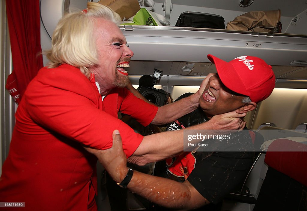 Sir <a gi-track='captionPersonalityLinkClicked' href=/galleries/search?phrase=Richard+Branson&family=editorial&specificpeople=220198 ng-click='$event.stopPropagation()'>Richard Branson</a> hugs Tony Fernandes after spilling a tray of drinks on him before their flight to Kuala Lumpur at Perth International Airport on May 12, 2013 in Perth, Australia. Sir <a gi-track='captionPersonalityLinkClicked' href=/galleries/search?phrase=Richard+Branson&family=editorial&specificpeople=220198 ng-click='$event.stopPropagation()'>Richard Branson</a> lost a friendly bet to AirAsia Group Chief Executive Officer Tony Fernandez after wagering on which of their Formula One racing teams would finish ahead of each other in their debut season of the 2010 Formula One Grand Prix in Abu Dhabi and that the loser would serve as a female flight attendant on board the winner's airline.