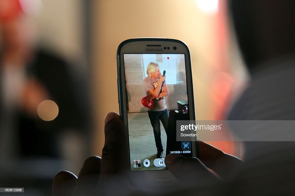 Sir <a gi-track='captionPersonalityLinkClicked' href=/galleries/search?phrase=Richard+Branson&family=editorial&specificpeople=220198 ng-click='$event.stopPropagation()'>Richard Branson</a> is filmed on a smartphone during his visit to the new Virgin Active Sandton under construction on February 27, 2013, in Johannesburg, South Africa.