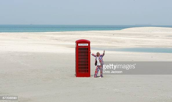 Sir Richard Branson poses next to a phone box during a photocall on a stretch of sand on the manmade island known as England in new development the...