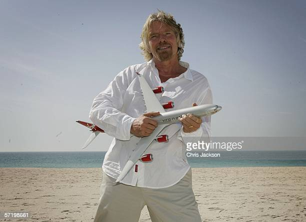 Sir Richard Branson poses with a model jet on the Burj Al Arab beach on the day the inaugural Virgin Atlantic flight from Londons Heathrow arrived at...