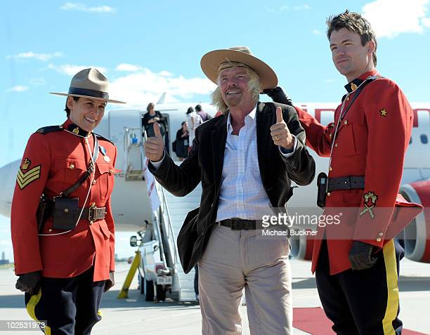 Sir Richard Branson poses with members of the Royal Canadian Mounted Police in front of 'Air Drake' to celebrate Virgin America's first international...