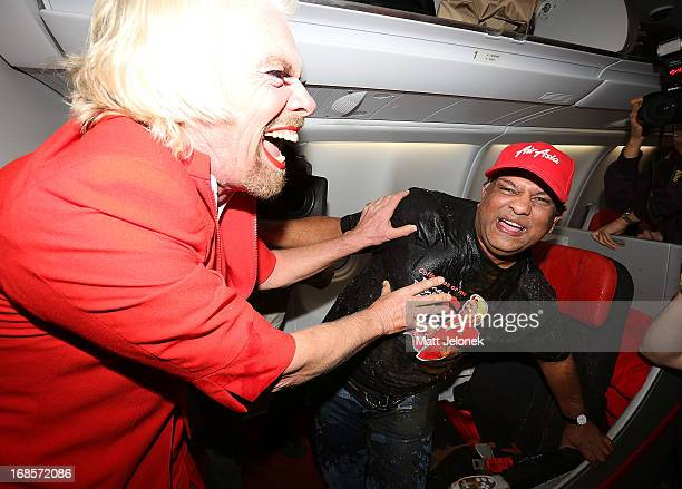 Sir Richard Branson pours drinks on AirAsia CEO Tony Fernandes on board a flight to Kuala Lumpur at Perth International Airport on May 12 2013 in...