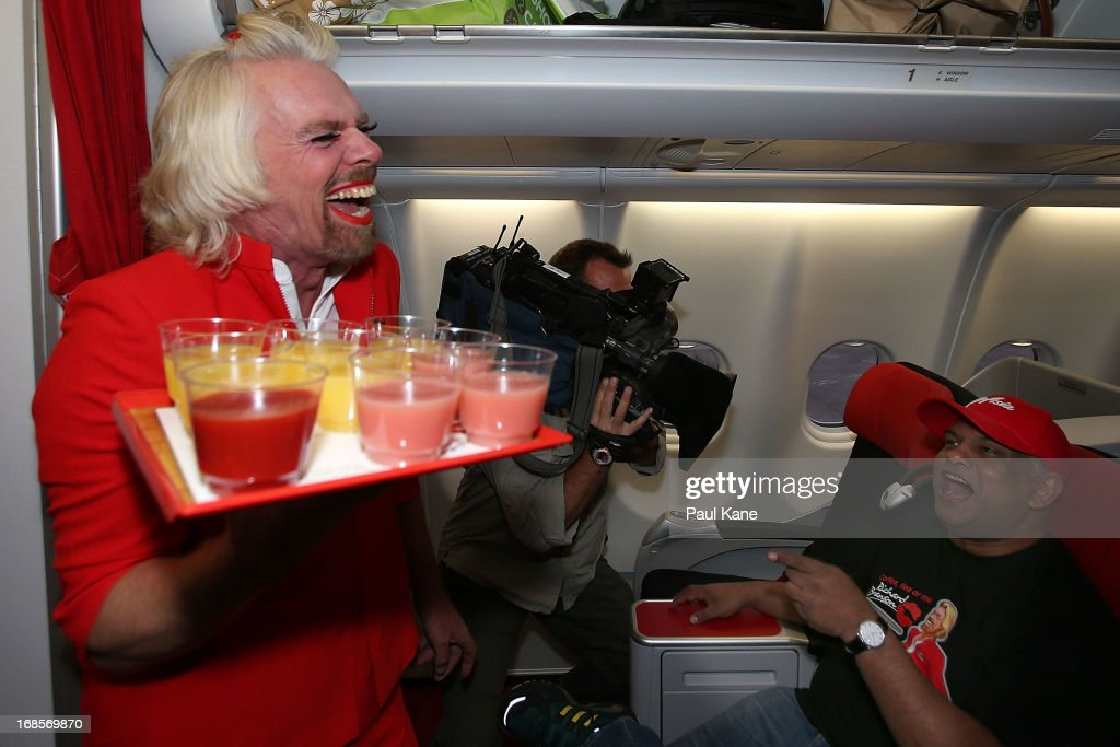 Sir <a gi-track='captionPersonalityLinkClicked' href=/galleries/search?phrase=Richard+Branson&family=editorial&specificpeople=220198 ng-click='$event.stopPropagation()'>Richard Branson</a> serves drinks to Tony Fernandes prior to their flight to Kuala Lumpur at Perth International Airport on May 12, 2013 in Perth, Australia. Sir <a gi-track='captionPersonalityLinkClicked' href=/galleries/search?phrase=Richard+Branson&family=editorial&specificpeople=220198 ng-click='$event.stopPropagation()'>Richard Branson</a> lost a friendly bet to AirAsia Group Chief Executive Officer Tony Fernandez after wagering on which of their Formula One racing teams would finish ahead of each other in their debut season of the 2010 Formula One Grand Prix in Abu Dhabi and that the loser would serve as a female flight attendant on board the winner's airline.