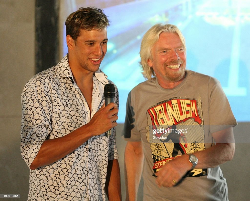 Sir Richard Branson (R) smiles beside Chad Le Clos during his visit to the new Virgin Active Sandton under construction on February 27, 2013, in Johannesburg, South Africa.