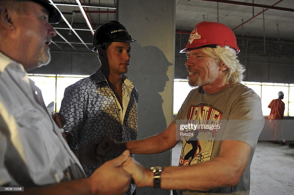 Sir Richard Branson (R) speaks to Bert, watched by Chad Le Clos, during his visit to the new Virgin Active Sandton under construction on February 27, 2013, in Johannesburg, South Africa.