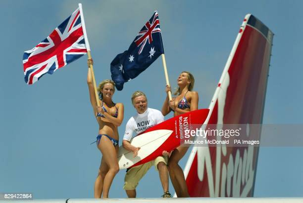 Sir Richard Branson stands on the wing of his new aircraft with two models holding flags from the UK and Australia after he landed at Sydney...