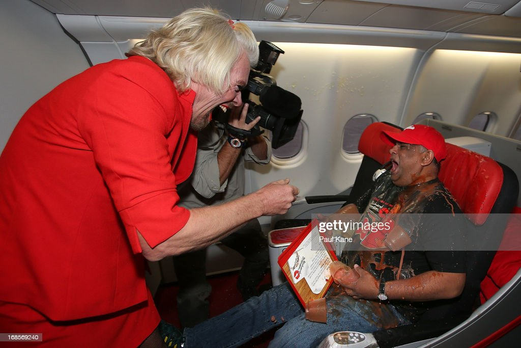 Sir <a gi-track='captionPersonalityLinkClicked' href=/galleries/search?phrase=Richard+Branson&family=editorial&specificpeople=220198 ng-click='$event.stopPropagation()'>Richard Branson</a> tips a tray of drinks onto Tony Fernandes prior to their flight to Kuala Lumpur at Perth International Airport on May 12, 2013 in Perth, Australia. Sir <a gi-track='captionPersonalityLinkClicked' href=/galleries/search?phrase=Richard+Branson&family=editorial&specificpeople=220198 ng-click='$event.stopPropagation()'>Richard Branson</a> lost a friendly bet to AirAsia Group Chief Executive Officer Tony Fernandez after wagering on which of their Formula One racing teams would finish ahead of each other in their debut season of the 2010 Formula One Grand Prix in Abu Dhabi and that the loser would serve as a female flight attendant on board the winner's airline.