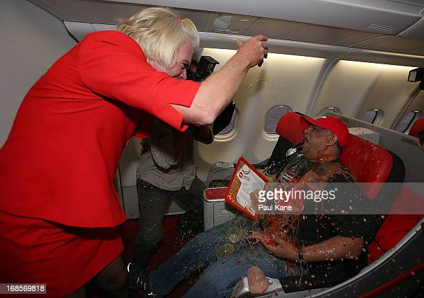 Sir Richard Branson tips a tray of drinks onto Tony Fernandes prior to their flight to Kuala Lumpur at Perth International Airport on May 12 2013 in...