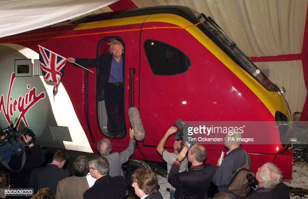 Sir Richard Branson waves the Union Flag during the launch of his new Virgin train Maiden Voyager in Bruges Belgium *05/03/01 Rail fares on Virgin...