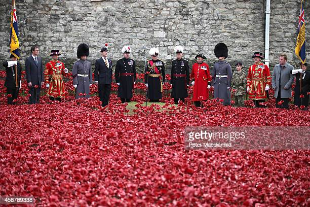 Sir Richard Dannatt stands with Military cadet Harry Alexander Hayes and artists Tom Piper and Paul Cummins after the last ceramic poppy was placed...