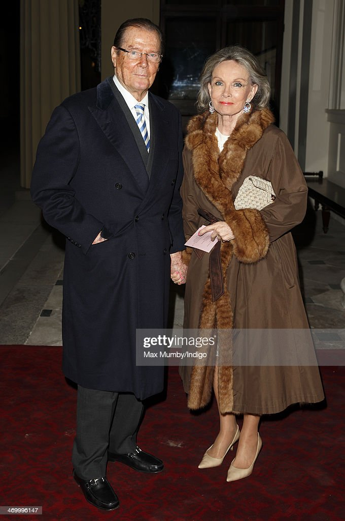 Sir Roger Moore and Kristina Tholstrup attend a Dramatic Arts reception hosted by Queen Elizabeth II at Buckingham Palace on February 17, 2014 in London, England.