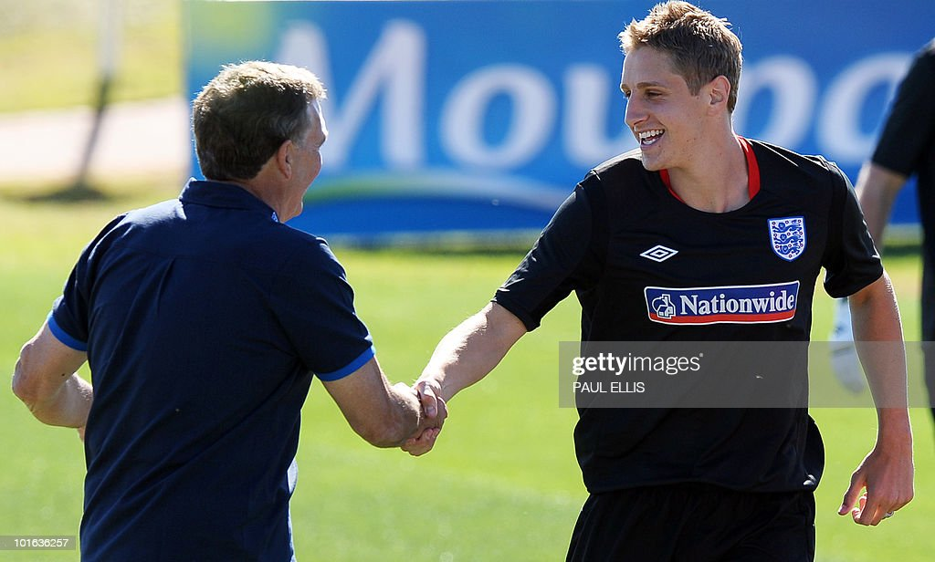 Sir Trevor Brooking (L) welcomes replacement defender Michael Dawson as he arrives for a training session at the Royal Bafokeng Sports Campus near Rustenburg on June 5, 2010. Dawson was flown from England to replace captain Rio Ferdinand after he injured his knee during the team's first training session in the country on the eve.