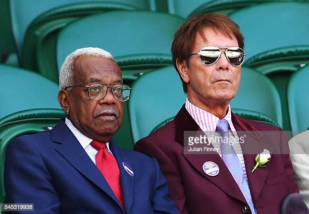 Sir Trevor McDonald and Sir Cliff Richard look on from Centre Court during the Ladies Singles Semi Final match match between Serena Williams of The...