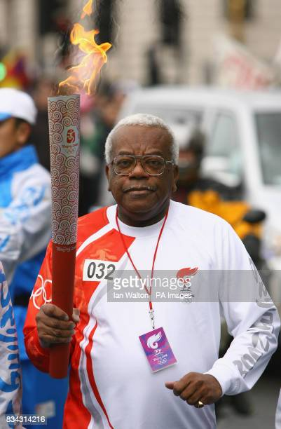 Sir Trevor McDonald carries the Olympic torch during its relay journey across London on its way to the lighting of the Olympic cauldron at the O2...