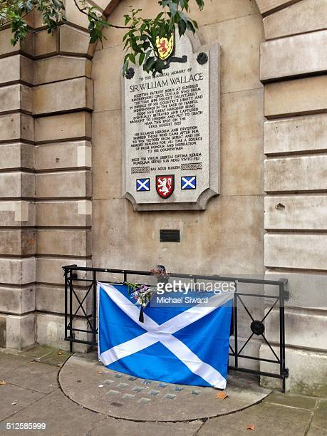 Sir William Wallace's Memorial with flowers and Scottish Flag at a site of his execution near St Bartholomew's Hospital in Central London