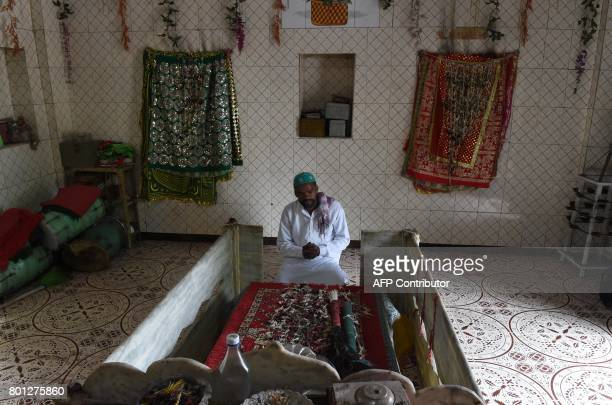 Sirajbhai Siddi offers prayers at the Hazrat Pir Baba Gaur shrine as he marks Eid alFitr in Ahmedabad on June 26 2017 Siddis are believed to be the...