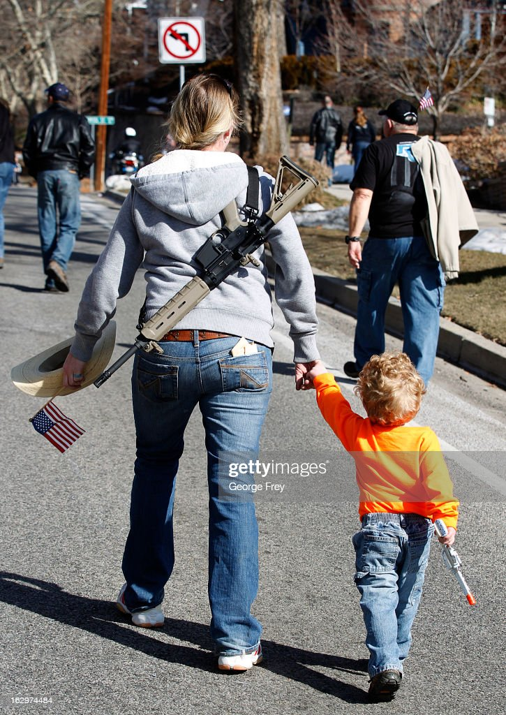 Siri Davidson (L) and her son Keaton walk up State Street, with an AR-15 she got for Valentine's Day, to a gun rights rally at the Utah State Capitol on March 2, 2013 in Salt Lake City, Utah. The rally attracted several hundred people for the march to the Utah Capitol in favor of 2nd Amendment rights as gun control supporters call for more limits and bans on assault weapons.