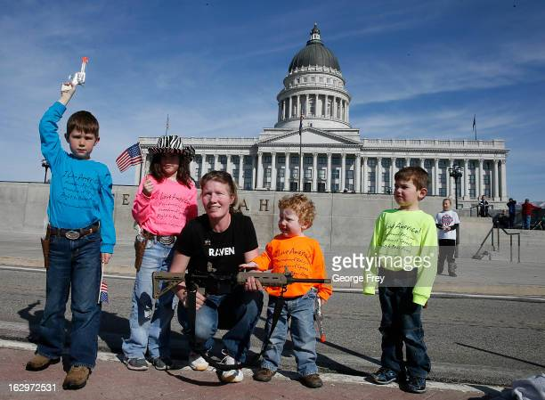 Siri Davidson center and her children left to right Alexander Eliza Keaton Porter pose for a picture with her AR15 that she got for a gift for...