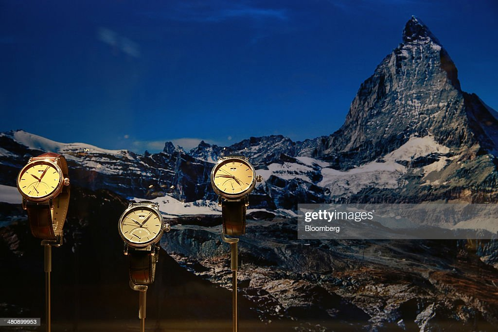Sirius Retrograde Day wristwatches, produced by Chronoswis AG, sit on display in front of a picture of the Swiss Matterhorn mountain, at the company's booth during the Baselworld luxury watch and jewelry fair in Basel, Switzerland, on Thursday, March 27, 2014. Over 1,400 companies from the watch, jewelry and gem industries will display their latest innovations and products to more than 120,000 visitors at this year's luxury show. Photographer: Gianluca Colla/Bloomberg via Getty Images