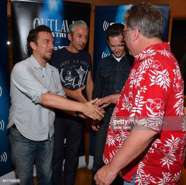 SiriusXM Host Mojo Nixon greets JD McPherson after Recording Artist JD McPherson performs for SIRIUSXM's Outlaw Country channel VIPs at Addiction...