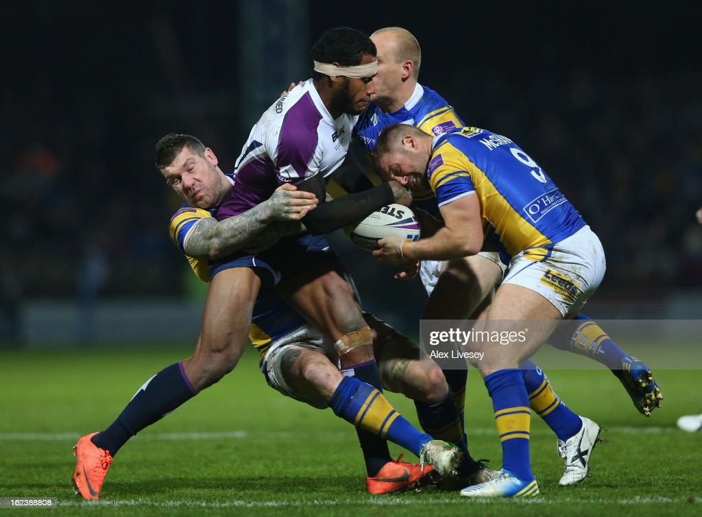 Sisa Waqa of Melbourne Storm is tackled by Paul McShane and Brett Delaney of Leeds Rhinos during the World Club Challenge match between Leeds Rhinos and Melbourne Storm at Headingley Carnegie Stadium on February 22, 2013 in Leeds, England.