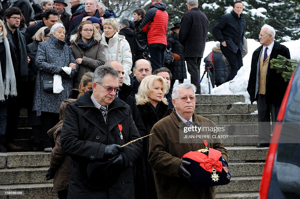 Sissi Herzog (C), the wife of French climber Maurice Herzog follows the hearse carrying her husband's coffin after his funeral ceremony, on December 20, 2012 at the Saint-Michel church in Chamonix, French Alps. Maurice Herzog, the French climber who conquered Annapurna in the first recorded ascent of a peak above 8,000 metres, has died at the age of 93, on December 14.