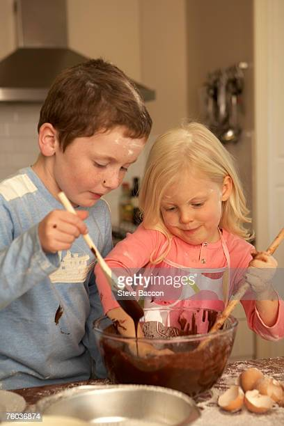 Sister and brother (4-5,8-9) baking in kitchen