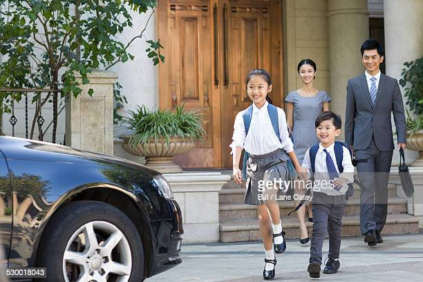 Sister and brother holding hands going to school