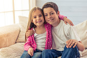 Cute little girl and her brother are hugging, looking at camera and smiling, sitting on sofa at home