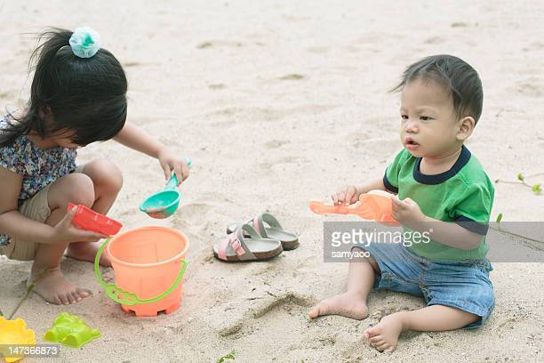 Sister and brother playing sands at the beach