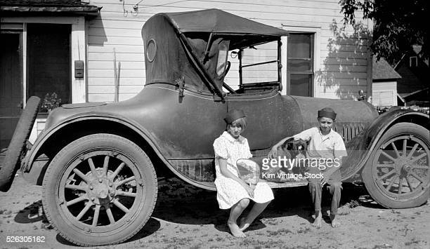 Sister and brother sit on their family car with the dog somewhere in Nebraska in the 1930s