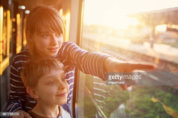 Sister and brother travelling on train