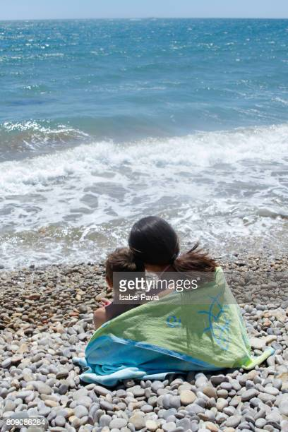Sister and brother wrapped in towel at beach