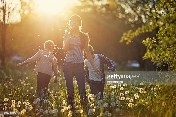 Sister and brothers enjoying spring dandelion field