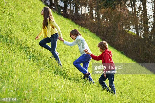 Sister and younger brothers climbing up grassy field