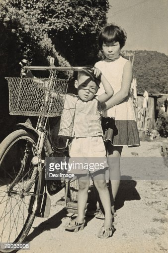Sister, brother and bicycle : Stock Photo