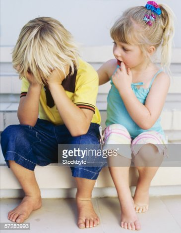 Sister comforting her brother : Stock Photo