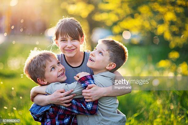 Sister embracing younger brothers in dandelion field