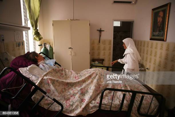 Sister Gloria Flores checks in on a patient at the Hermanitas de los Ancianos Desamparados facility which cares for the elderly as they deal with the...
