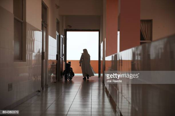 Sister Gloria Flores walks through the halls of the Hermanitas de los Ancianos Desamparados facility which cares for the elderly as they deal with...