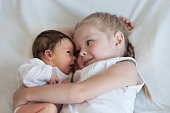 5 years old sister hugs her younger 2 weeks old brother