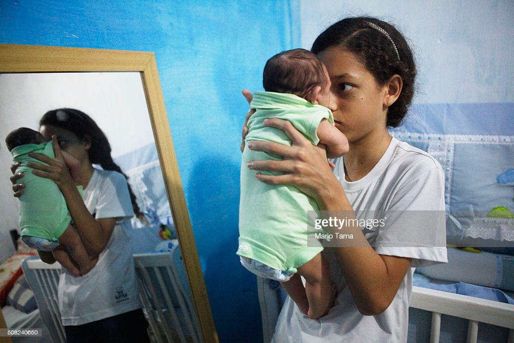 Sister Jennipher Karine plays with her brother Juan Pedro, 2-months-old, who has microcephaly, in front of the mirror on February 3, 2016 in Recife, Pernambuco state, Brazil. In the last four months, authorities have recorded thousands of cases in Brazil in which the mosquito-borne Zika virus may have led to microcephaly in infants. Microcephaly results in an abnormally small head in newborns and is associated with various disorders. The state with the most cases is Pernambuco, whose capital is Recife, and is being called the epicenter of the outbreak.