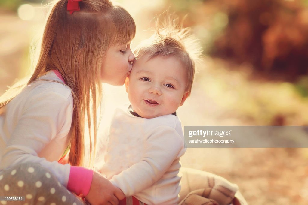 sister kissing her brother in winter sunshine