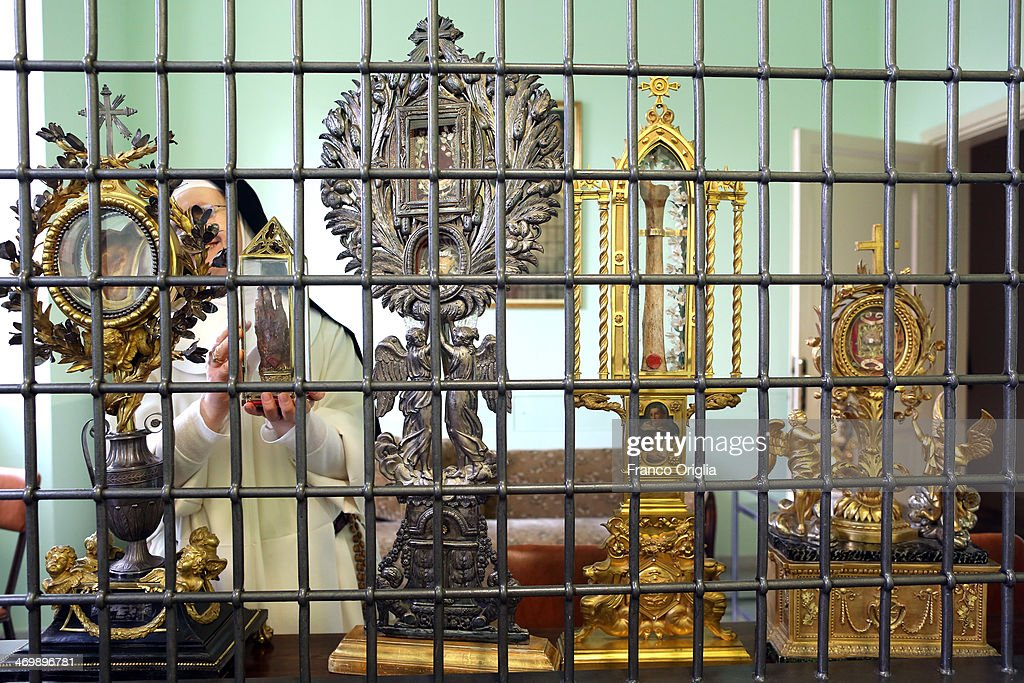 Sister Maria Domenica framed by holy relics (Catherine's scapule, finger of St Peter of Verona and St Thomas' shinbone) holds the hand of Saint Catherine of Siena (1347-1380) at the cloistered convent of St. Mary of the Rosary on February 6, 2014 in Vatican City, Vatican. The Dominican Nuns of St. Mary of the Rosary monastery supervise relics since the papacy of Pius IX (1860ca). Relics may be legitimately obtained from Church sources, the Vicariate in Rome, the religious Order of the Saint involved and the shrine of the Saint involved. When this is done, a donation is usually expected to cover the cost of the metal container (theca) that contains the relic, but in any case, a profit cannot legitimately be made from the sale of relics by anyone.