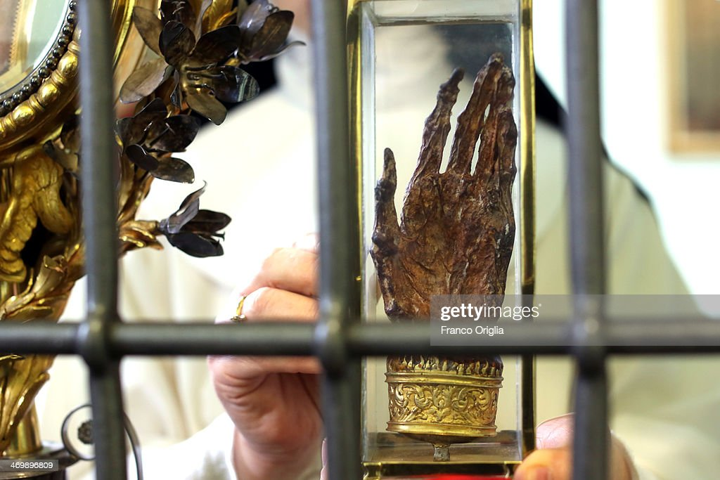 Sister Maria Domenica holds the hand of Saint Catherine of Siena (1347-1380) at the cloistered convent of St. Mary of the Rosary on February 6, 2014 in Vatican City, Vatican. The Dominican Nuns of St. Mary of the Rosary monastery supervise relics since the papacy of Pius IX (1860ca). Relics may be legitimately obtained from Church sources, the Vicariate in Rome, the religious Order of the Saint involved and the shrine of the Saint involved. When this is done, a donation is usually expected to cover the cost of the metal container (theca) that contains the relic, but in any case, a profit cannot legitimately be made from the sale of relics by anyone.