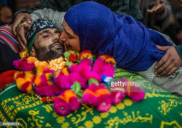 Sister of Rayees Ahmad a militant who was killed in a gun battle with the Indian government forces pecks his body during his funeral on November 20...