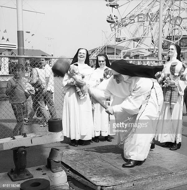 Sister Patrick Joseph puts all her might into the heavy hammer as she tries to ring the bell during the 30th Annual New York City Police Anchor Club...