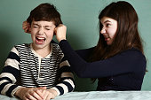 sister pull brother ear as a loss in argument wage close up photo
