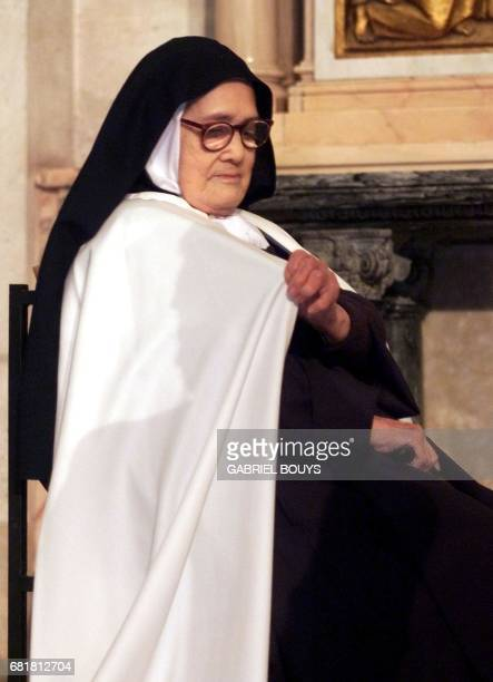 Sister Santa Maria Lucia of the Immaculate Heart adjusts her cape near the grave of Francisco Marto before she meets Pope John Paul II 13 May 2000 in...